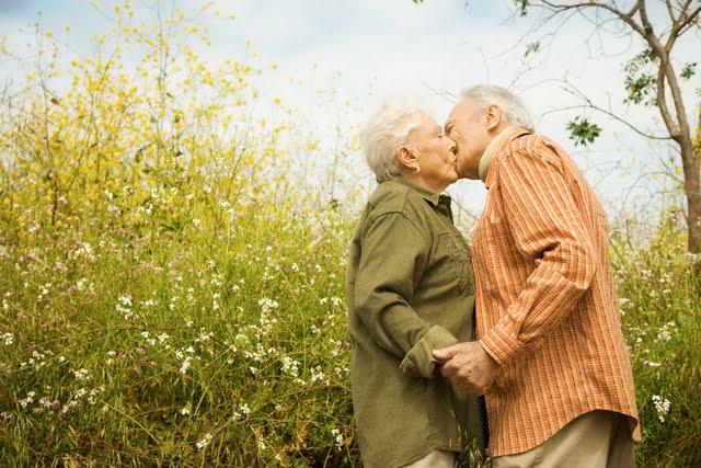 Elderly Couple Kissing in Meadow